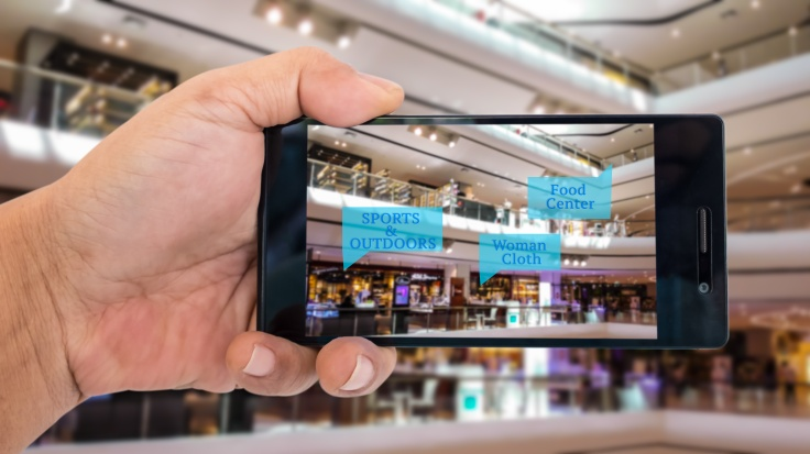 Augmented reality application for retail business concept. Hand holding smart phone with A/R application on screen to finding shop in department stroe. Represent A/R application in business.